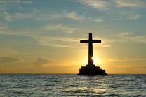 Catholic cross water sunset blue sky